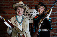 NWA Democrat-Gazette/DAVID GOTTSCHALK - 2/13/15 - Mary Young (left) and Kathy Babb display rifles Friday February 13, 2015 at the U.S. Marshals Office in Fort Smith that will be included in the activities of the U.S. Marshals Stampede Kickin' up the Dust fundraising gala on March 14, 2015.