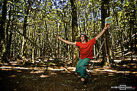 Slackliner James Clulow posing for the camera with a painter's pad and brush while balancing on a rodeo line.  New Zealand.