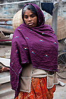 Urmila Maurya, 38, stands in front of the pile of rubble which was once her home in the institutional area of Lodi Colony, an upmarket area in New Delhi, India on 03 January 2012. A mother of 2, she spends her days on the pavement stringing flowers into garlands for devotees at the nearby Hindu temple. At night, she lays down on the same plastic tarpaulin she uses for the flowers but claims that the police come and tear it up in an attempt to discourage her from squatting in the open. Photo by Suzanne Lee for The National
