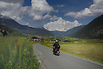 Motor cyclist on country lane passing spring meadows driving towards Tarranz. Imst district, Tyrol, Tirol, Austria.