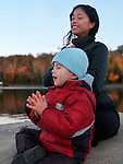 Cute three year old boy and a young woman sitting in lotus pose meditating in autumn nature on a shore of a lake. Ontario, Canada.