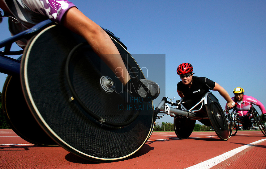 (Left to right) Susannah Scaroni of the United States, Patrice Dockery of Ireland, and Ivonne Reyes of Mexico round a turn on the Lakewood Stadium track during a 5000-meter run on Sunday, July 2, 2006. Over 200 athletes entered the U.S. Paralympic Track & Field National Championships this year. Many of them will be racing again in the Peachtree Road Race on Tuesday.