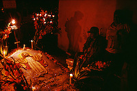 Day of the Dead vigil at a family grave with candles and flowers. Dia de los Muertos, Day of the Dead, is Mexico's most characteristic fiesta where it is believed that souls of the dead return to the earth. Families build alters in their homes and visit the cemeteries to commune with their dead loved ones taking flowers and their favorite foods. An atmosphere of celebration in this small community outside Oaxaca, is complete with music. Families spend the night in the cemetery lighting candles, burning incense, talking, eating, and.singing. Some grave sites such as this one had three dimensional sand paintings done just for the celebration.