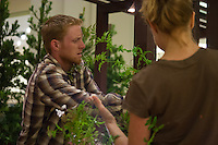 "Two students work to artfully wrap a vine around a post at Orange Coast College's Ornamental Horticulture Club's in-progress installation at the 2012 South Coast Plaza Spring Garden Show in Costa Mesa, CA.  The theme for this year's show is ""healing gardens"", and the OCC team is installing a ""garden for the blind,"" which will be complete with a braille world globe and braille labels.  This picture was taken Tuesday April 25, 2012 at ~11pm, as the team was working frantically to meet their Thursday-morning deadline.  This image was taken at a high ISO using the ambient light in the dim mall, so it's noisier than my typical images (and thus I'd recommend against printing it large)."