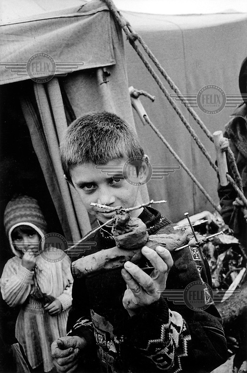 ©Heidi Bradner/Panos Pictures..Chechnya. A Chechen boy now living in a refugee camp shows off his new skill, making attack helicopter from mud and sticks of wood.