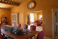 A large arch separates the rich yellow dining room from the sitting room in this Tuscan house