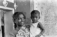 A mother and child wait outside the grand temple in Tiruvannamalai, Tamil Nadu, India on April 13, 1999, the eve of Tamil Nadu's new year. Thousands of people came to Tiruvannamalai to celebrate Tamil Nadu's new year.