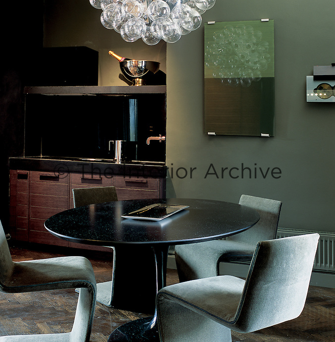 A contemporary green kitchen diner with wooden units and a grey upholstered chairs around an Eero Saarinen dining table.