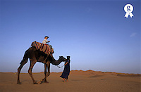 Morocco, Erg Chebbi, Touareg man leading boy (2-3 years) riding camel in Sahara Desert (Licence this image exclusively with Getty: http://www.gettyimages.com/detail/sb10068805v-001 )