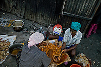 Haitian women prepare sausages to be sold in the La Saline market, Port-au-Prince, Haiti, 14 July 2008. Every day thousands of women from all over the city of Port-au-Prince try to resell supplies and food from questionable sources in the La Saline market. The informal sector significantly predominate within the poor Haitian economics and the regular shops virtually do not exist. La Saline is the largest street market area in Port-au-Prince.