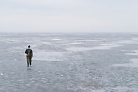 Lone ice fisherman walking out on frozen Curonian Lagoon, Nida, Lithuania