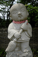 A jizo statue on Mount Takao. He is holding a sweeping brush to remind people to take home their rubbish.