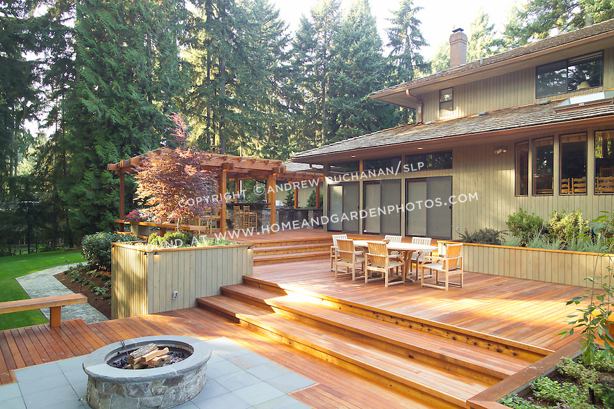 A 1700 square foot, 2-level deck, outdoor kitchen, and firepit complete the outside of this ranch-style home tucked among towering fir trees in a Seattle suburb. Design by Sander Groves Landscapes, Inc.
