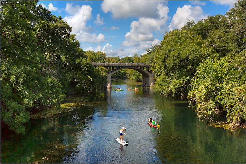 White clouds drift over a Barton Springs, a tributary to Lady Bird Lake. Beneath the pedestrian bridge from which I was photographing this Zilker Park are, paddle boarders and canoers explore the clear waters. This Austin, Texas, sanctuary is a favorite of Austinites and tourists in the summer and all year.