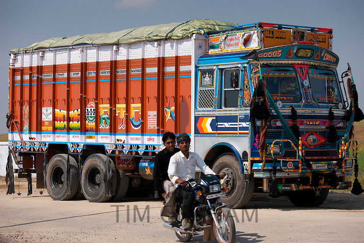 Indian motorcyclist rides past Tata trucks at Rasulpura in Sawai Madhopur, Rajasthan, Northern India