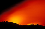 Hikers watching lava flow enter the Pacific Ocean at night, Hawaii Volcanoes National Park, The Big Island, Hawaii USA