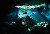 RX0622-D. scuba diver (model released) swims between curtains of light shining down through the opening to a cenote, the entranceway to caverns and tunnels waiting to be explored. Riviera Maya, Yucatan Peninsula, Mexico.<br /> Photo Copyright &copy; Brandon Cole. All rights reserved worldwide.  www.brandoncole.com