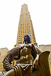 Manhattan, New York, U.S. - May 21, 2014 - At Rockefeller Plaza is bronze Mankind statue, Maiden, by artist Paul Manship, with 30 Rockefeller Center looms behind, during a pleasant Spring Day, though skies are cloudy.