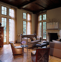 Sunlight is filtered through the sheer curtains in this elegant double height living room