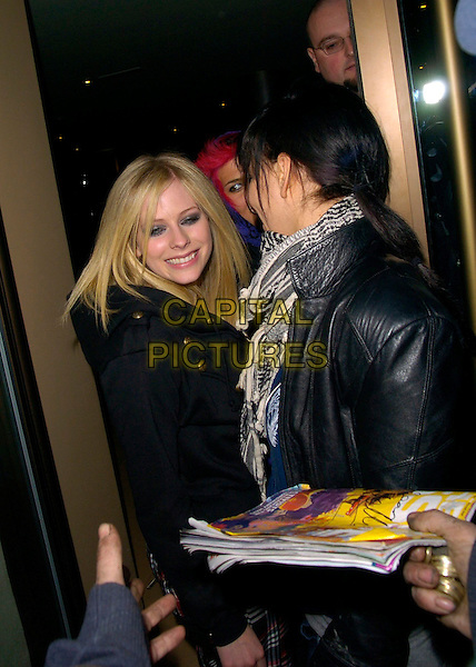 AVRIL LAVIGNE.Spotted at the Mayfair Hotel, London, UK..March 21st, 2007.half length looking over shoulder entourage black coat .CAP/CAN.©Can Nguyen/Capital Pictures