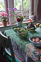 There are flowers everywhere, in a pot on the window sill, in a vase on the table, and as motifs on a ceramic jar and tablecloth