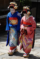 Two beautiful Japanese tourists walk the cobbled streets of Gion in the elaborate kimono of geisha apprentices, or maiko, Kyoto, Japan.