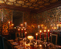 A glamorous dining room with walls of painted and gilded leather and a trompe l'oeil ceiling