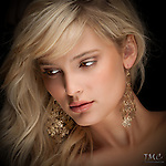Closeup of beautiful young blonde woman with brown eyes and gold earrings