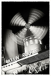 Moulin Rouge at night in Paris France with spinning windmill