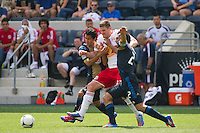 Kenny Cooper (33) of the New York Red Bulls is defended by Josue Martinez (17) and Carlos Valdes (2) of the Philadelphia Union. The New York Red Bulls defeated the Philadelphia Union  3-2 during a Major League Soccer (MLS) match at PPL Park in Chester, PA, on May 13, 2012.