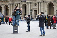 Young tourists having fun trying to balance on posing plinth outside the Louvre Museum, Central Paris, France
