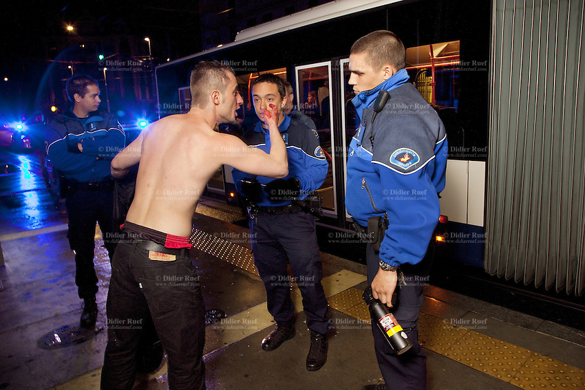 """Switzerland. Geneva. Jonction neighborhood. Three police officers listen to a bloody and bare-chested man from Kosovo. The young man hurts himself on the right hand in a fight during a bus ride in the late night. The policemen will let him go freely back home. The policeman (R) holds a pepper spray in his hand. Pepper spray, also known as OC spray (from """"Oleoresin Capsicum""""), OC gas, and capsicum spray, is a lachrymatory agent (a chemical compound that irritates the eyes to cause tears, pain, and even temporary blindness) used in policing. Its inflammatory effects cause the eyes to close, taking away vision. This temporary blindness allows officers to more easily restrain subjects. 6.05.12 © 2012 Didier Ruef"""