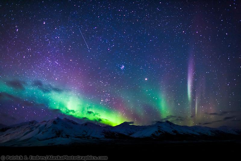 Colorful aurora borealis over the mountains near Chandalar Shelf, Brooks Range Alaska, hovering over the Arctic National Wildlife Refuge.