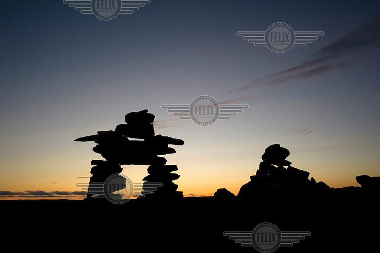 An Inuksuk (Inuit stone cairn) in the form of a human being called an Inunnguaq near the village of Kuujjuaq. Inuksuit (plural of Inuksuk) vary in shape and size, they have deep roots in the Inuit culture, often figures holding spirit, sacred meaning and direction..