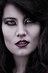 Close-up portrait of a young woman, vampire like, staring at the camera.