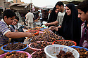 Iraqis rush to purchase dates before the Ramadan iftar meal inside the thriving central market place in the Amil neighborhood in Southwest Baghdad August 23, 2010. Through an increase in Iraqi security force checkpoints and gated communities, Iraqis have enjoyed a vast improvement in terms of security over the past two years in areas like Amil, which previously had been sectarian battlefields with Iraqis forced to remain inside their homes for protection.   .