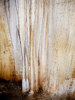 STALACTITES &amp; STALAGMITES IN LIMESTONE CAVERN <br /> Queen's Chamber, Translucent drapery<br /> Calcium carbonate deposits (Stalactites) hang from the top of limestone caverns, formed by the dripping of mineralized solutions. Corresponding columnar deposits (Stalagmites) are built upward. Queens Chamber, Carlsbad.