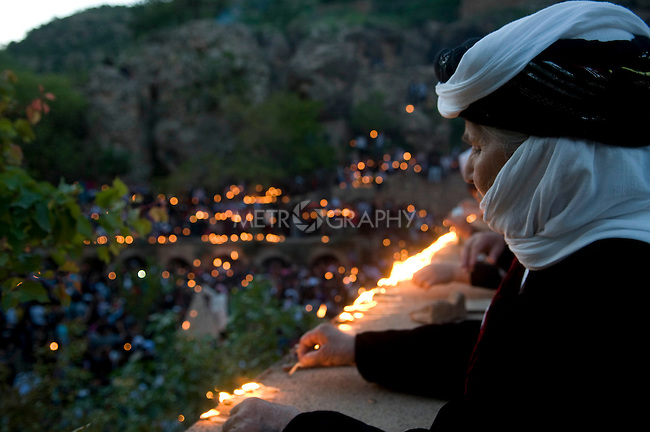 LALISH VALLEY, IRAQ: Yezidi woman lights a candle wick dipped in oil...The Yezidis, a minority religious group found in northern Iraq, celebrate Chwar Shema Sur (Red Thursday), as part of their New Year festival.  The Yezidis are the religious descendants of Zoroastrians and as a religious minority in Iraq are often targeted by terrorists.