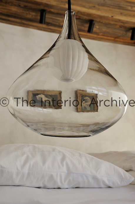 Glass pendant lamps by Isabel Hamm illuminate the bed