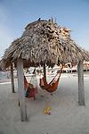 hammocks hanging under a thatched palapa at Ramon's Village Resort in San Pedro, Ambergris Caye, Belize