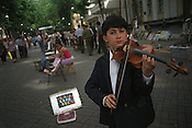 Young boy plays his violin for money in a street market in Tashkent. Many people come here to sell belongings, art or to busk for money. Tashkent, Uzbekistan