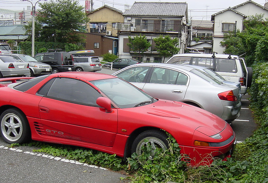 Driver leaves car in car-park for so long that vegetation has had time to grow up its wheels.