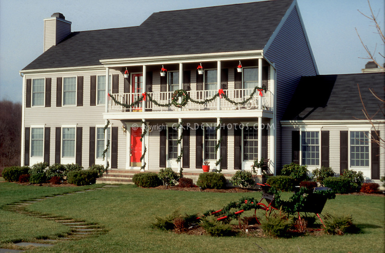 House with holiday trimmings, ornamental sleigh in front yard, curb appeal, outdoor Christmas decorations, garland and wreaths, poinsettias, old-fashioned, lawn with path, classic traditional home landscaping in winter December outdoors