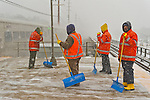 Merrick, New York, U.S. January 21, 2014. Pausing briefly for safety's sake as a train rushes into the LIRR Merrick Train Station, Maintenance of Way (MOW) staff members of the Metropolitan Transit Authority (MTA) shovel snow as it falls heavily on the windy elevated platform. The Metropolitan Transit Authority added extra afternoon trains to Long Island Rail Road. Long Island towns declared a snow emergency, with up to 10 inches of snow expected.