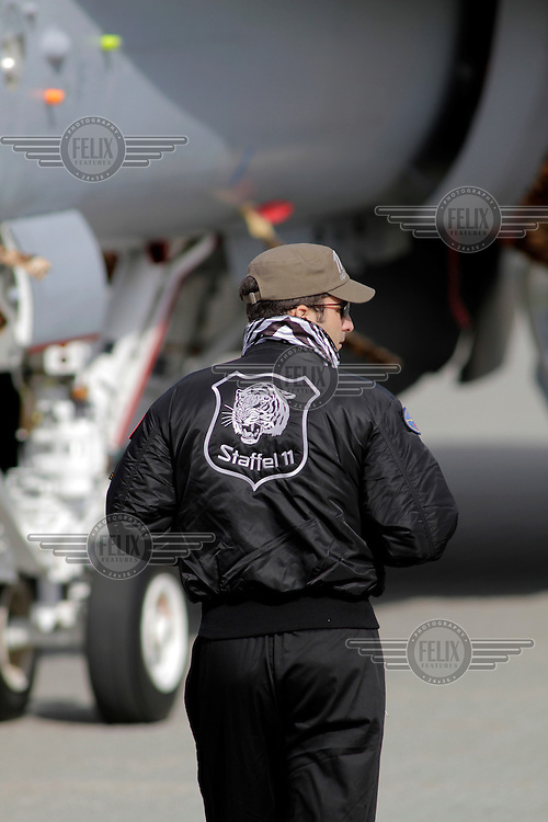Crew (pilot ?) of a Swiss F-18 Hornet fighter jet with a tiger decorated jacket. Tiger Air show.  Nato Tiger Meet is an annual gathering of squadrons using the tiger as their mascot. While originally mostly a social event it is now a full military exercise. Tiger Meet 2012 was held at the Norwegian air base Ørlandet.