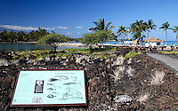 Walkway around the historic fish pond at Anaehoomalu Beach in Waikoloa, with Ocean Sports shop and Anaehoomalu Beach in background