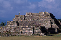 Tourists walk along the top of Monte Alban, ruins of the ancient Zapotec capital overlooking the city of Oaxaca. First occupied around 500 BC by Zapotecs, there are cultural connections with the Olmecs.  Development began with the building of temples and palaces and the population reached  10,000.  At it's peak around 300-700 AD, the surrounding hills were terraced for dwellings and population was 25,000. It was a highly organized, priest-dominated society. The agriculture included chili, avocado, beans, the people also ate deer, rabbit and dog. It was abandoned around 700-950 AD as population dispersed. It was then used as burial grounds.