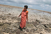 Beiataake Orea, a school teacher, stands on the beach at Tenoraereke village, examing an old sea wall destroyed by the sea and expressing her worry about the future of her island of Kiribati in the Pacific Ocean. The islands, and their way of life, are endangered by rising sea water levels which are eroding the fragile atoll, home to approximately 92,000 people.