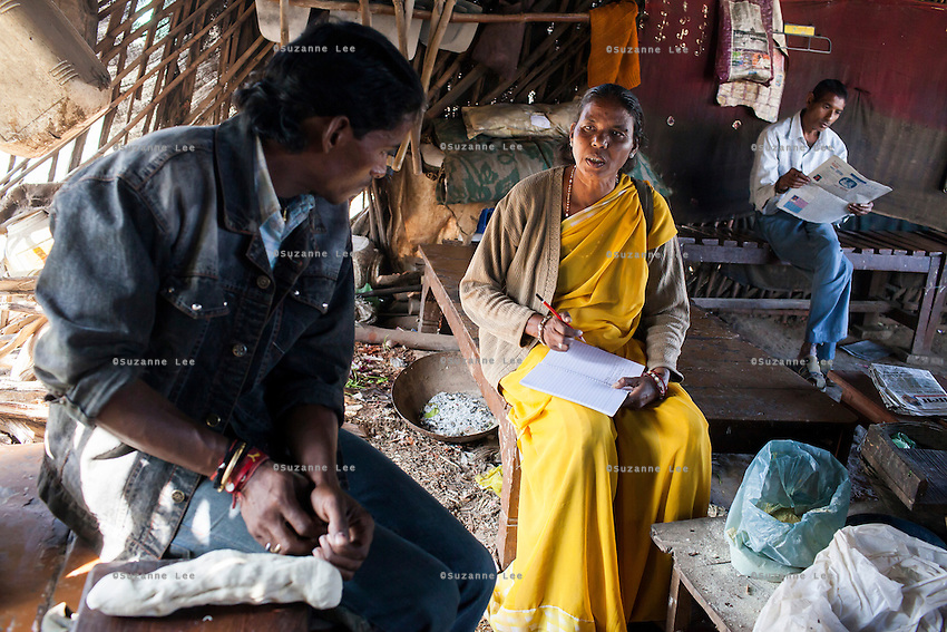 Shanti Adivasi (in yellow saree), 52, interviews a worker in a roadside food stall in Jawaharnagar area in Manikpur, Chitrakoot, Uttar Pradesh, India on 6th December 2012. Shanti used to be a wood gatherer, working with her parents since she was 3, and later carrying up to 100 kg of wood walking 12km from the dry jungle hills to her home to repack the wood which sold for 3 rupees per kg. After learning to read and write in an 8 month welfare course, at age 32, she became a reporter, joining Khabar Lahariya newspaper since its establishment in 2002, and making about 9000 rupees per month, supporting her family of 14 as the sole breadwinner. Photo by Suzanne Lee for Marie Claire France.