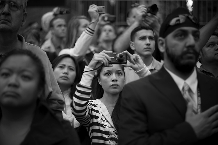 """© 2011  David Burnett .Contact Press Images.212 695 7750..September 11, 2011..New Yorkers and out of towners attend the 9/11 ceremonies, in the Financial district, New York City:  two jumbo TV screens brought the actual ceremony to those who were in the """"Public Space."""""""